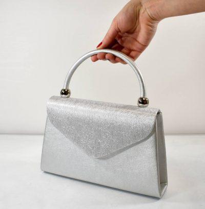 Extravagantná večerná kabelka v striebornej farbe s uchom do ruky a prídavným ramienkom
